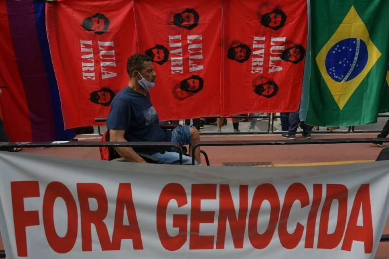 """A demonstrator passes by a banner reading """"Genocide out"""" during a protest against Brazilian President Jair Bolsonaro, in Sao Paulo, Brazil, on October 2, 2021 (AFP/NELSON ALMEIDA)"""