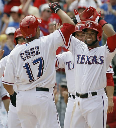 From back right to left, Texas Rangers' Elvis Andrus, Lance Berkman and David Murphy congratulate teammate Nelson Cruz (17) on a grand slam in the fifth inning of a baseball game against the Seattle Mariners in Arlington, Texas, Sunday, April 21, 2013. Texas won 11-3. (AP Photo/Brandon Wade)