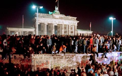 <span>In November 1989 thousands of young East Berliners crowded on top of the Berlin Wall, near the Brandenburg Gate </span> <span>Credit: Gerard Malie/AFP </span>
