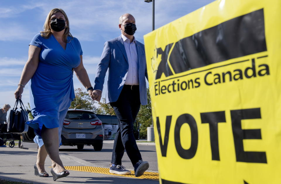 Conservative Leader Erin O'Toole and his wife Rebecca arrive to vote in the Canadian federal election in Bowmanville, Ontario on Monday, September 20, 2021. (Frank Gunn/The Canadian Press via AP)