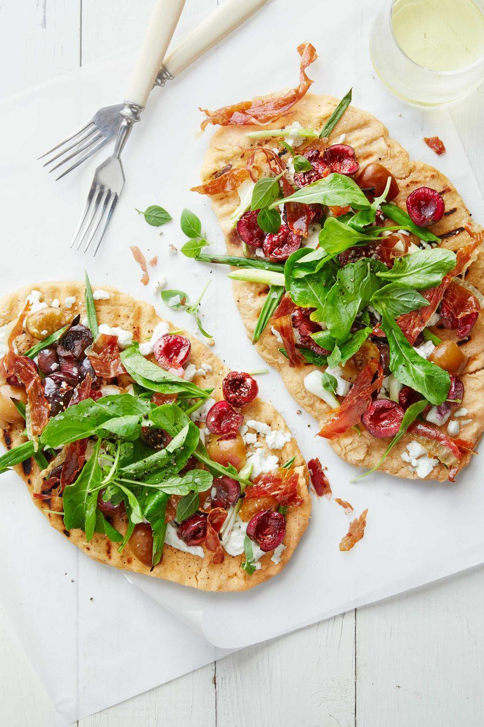 """<p>These crispy flatbreads achieve the perfect combo of salty, tangy and sweet in every bite.</p><p><strong><a href=""""https://www.countryliving.com/food-drinks/recipes/a38953/cherry-prosciutto-grilled-pizzas-recipe/"""" rel=""""nofollow noopener"""" target=""""_blank"""" data-ylk=""""slk:Get the recipe"""" class=""""link rapid-noclick-resp"""">Get the recipe</a>.</strong></p>"""