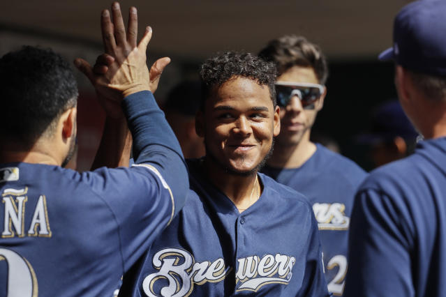 Milwaukee Brewers starting pitcher Freddy Peralta celebrates in the dugout after closing the eighth inning of a baseball game against the Cincinnati Reds, Wednesday, April 3, 2019, in Cincinnati. (AP Photo/John Minchillo)
