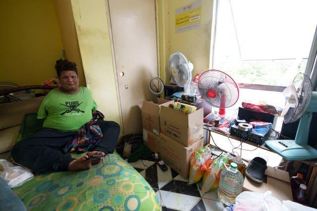 Mohamad Nor Abdullah, born without arms, sits near donated goods, right, in his rented room in Kuala Lumpur, Malaysia (Vincent Thian/AP)