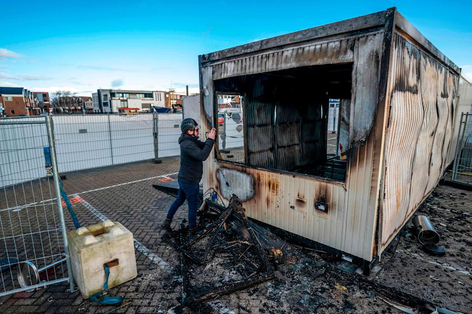 A man takes a photograph of a torched drive-in coronavirus test centre in the port UrkANP/AFP via Getty Images