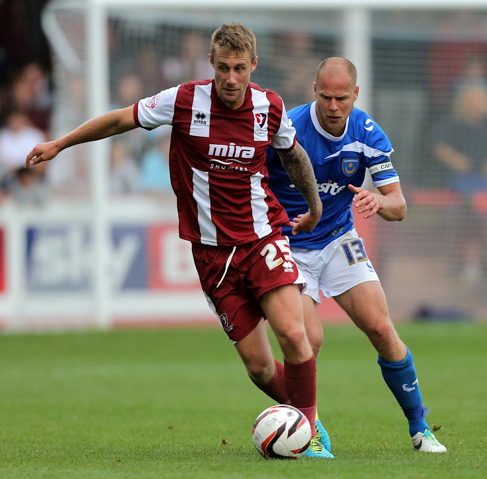 Cheltenham Town's David Noble on his debut holds off Portsmouth's Johannes Ertl during the Sky Bet Football League Two match at the Abbey Business Stadium, Cheltenham.