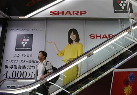 Man rides an escalator past Sharp Corp's advertisements at an electronics retail store in Tokyo