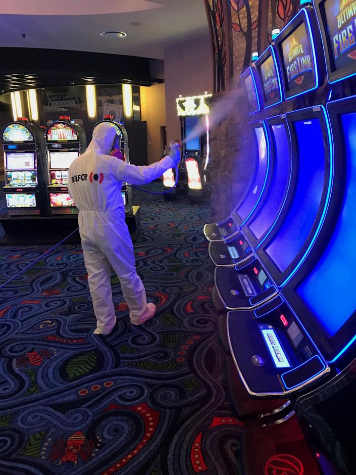 A worker for Belfor Property Restoration in Birmingham, Michigan, sprays disinfectant while deep cleaning a casino to remove any trace of the coronavirus.