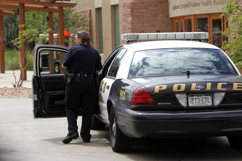 A University of Colorado Police officer gets into her patrol car on Thursday, Aug. 2, 2012, at the University of Colorado Medical Campus in Aurora, Colo. Suspected movie theater shooter James Holmes was studying neuroscience at the medical school and a psychiatrist there raised an alarm about his behavior. In the wake of a student's deadly attack at Virginia Tech five years ago, schools across the country put into place teams meant to bring together faculty and staff to notice and take action, when a student appears to be a threat. The school won't say if campus police ever were alerted to Holmes, or whether faculty or staff ivestigated his behavior.(AP Photo/Ed Andrieski)
