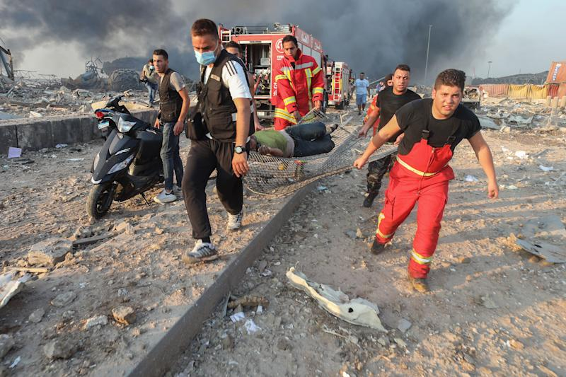 <strong>Firefighters carry an injured person from the scene following a large explosion at the Port of Beirut.</strong> (Photo: Bloomberg via Getty Images (Photographer: Hasan Shaban))