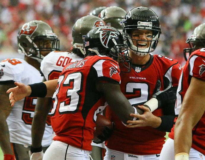 Atlanta Falcons quarterback Matt Ryan, right, celebrates his touchdown pass with Atlanta Falcons wide receiver Harry Douglas during the first half of an NFL football game against the Tampa Bay Buccaneers on Sunday, Oct. 20, 2013, in Atlanta. (AP Photo/Atlanta Journal-Constitution, Curtis Compton)