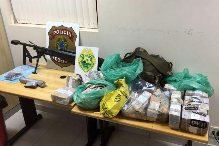 An assault rifle and money seized on April 24, 2017, after the robbery in Ciudad del Este, Brazil