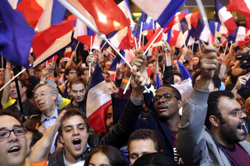 Head-tohead: Supporters of French centrist presidential candidate Emmanuel Macron react to the news (AP)