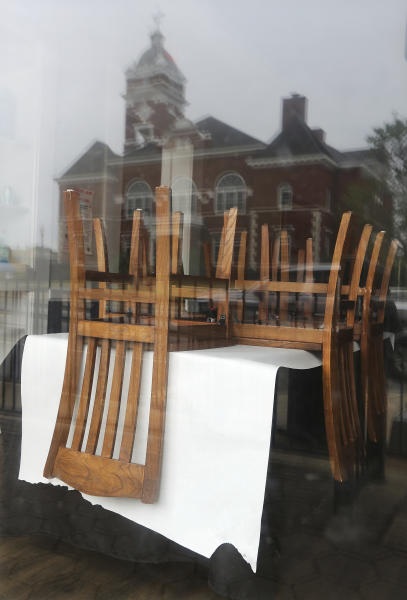 Chairs are stacked on top of tables, seen through the front windows of Minori's Italian Ristorante, which reflec the Forsyth County Courthouse across the street Wednesday, April 22, 2020, in Forsyth, Ga. The Monroe County Commission recently voted to urge Gov. Brian Kemp and President Donald Trump to begin reopening the economy by the end of the month, becoming one of the first local Georgia governments to formally demand a speedier end to coronavirus restrictions. On Friday, elective medical procedures may resume in Georgia, and barbershops, nail salons and gyms will reopen with restrictions. Limited in-restaurant dining will resume Monday. (Curtis Compton/Atlanta Journal-Constitution via AP)