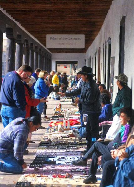 This undated image provided by the Santa Fe Convention and Visitors Bureau shows vendors at the Palace of the Governors in Santa Fe, N.M., selling jewelry, crafts and other wares. The Palace of the Governors, built in the 1600s as the seat of government for Spain's Southwestern territories, is now one of a half-dozen museums in Santa Fe devoted to history, culture and art. (AP Photo/Sante Fe Convention and Visitors Bureau, Chris Corrie)