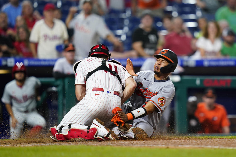 Baltimore Orioles' Pedro Severino, right, is tagged out at home by Philadelphia Phillies catcher J.T. Realmuto after trying to score on a single by Pat Valaika during the eighth inning of an interleague baseball game, Wednesday, Sept. 22, 2021, in Philadelphia. (AP Photo/Matt Slocum)