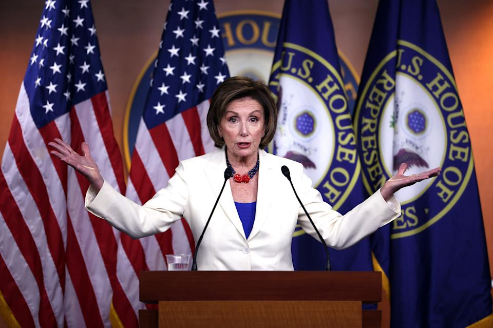 Nancy Pelosi stands at podium with arms extended