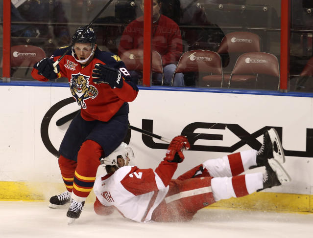 After knocking Detroit Red Wings' Brendan Smith to the ice, Florida Panthers' Tomas Kopecky (82) chases the puck during the first period of a NHL hockey game in Sunrise, Fla., Tuesday, Dec. 10, 2013. (AP Photo/J Pat Carter)