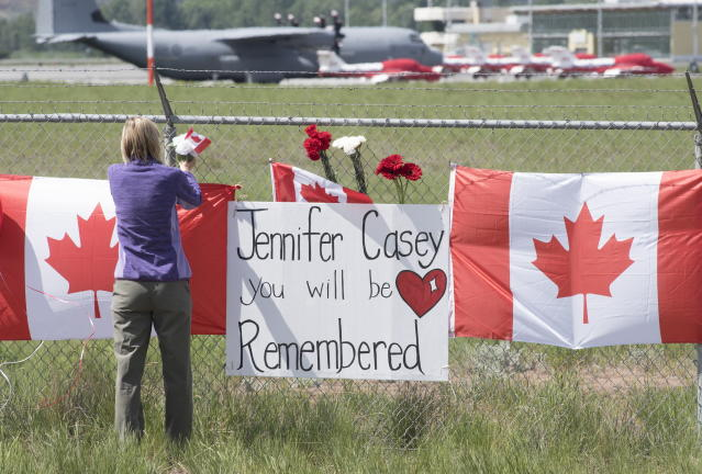 The Canadian Forces Snowbirds jets are seen in the background as a woman pays her respects in Kamloops, B.C., Monday, May 18, 2020. Capt. Jenn Casey died Sunday after the Snowbirds jet she was in crashed shortly after takeoff. The pilot of the aircraft is in hospital with serious injuries. (Jonathan Hayward/The Canadian Press via AP)