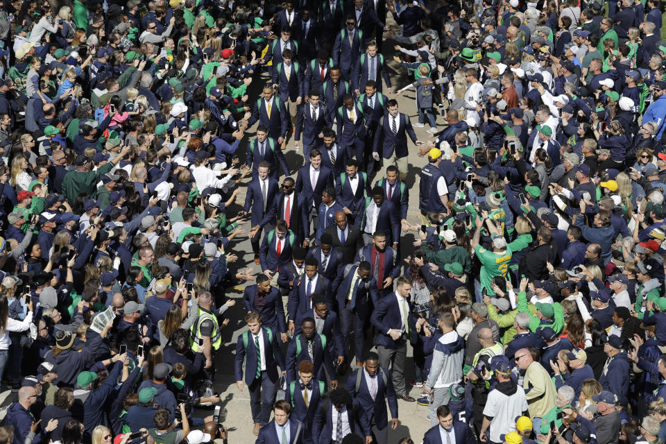 FILE - In this Oct. 5, 2019, file photo, Notre Dame players greet fans as they enter the stadium before an NCAA college football game against Bowling Green, in South Bend, Ind. College football fans will head back into stadiums this weekend. Along with binoculars, sunscreen and other essentials, some will pack facemasks and proof of vaccination. With the availability of COVID-19 vaccines, the pomp and pageantry of fall Saturdays are expected to return nearly everywhere across the country. (AP Photo/Darron Cummings, File)