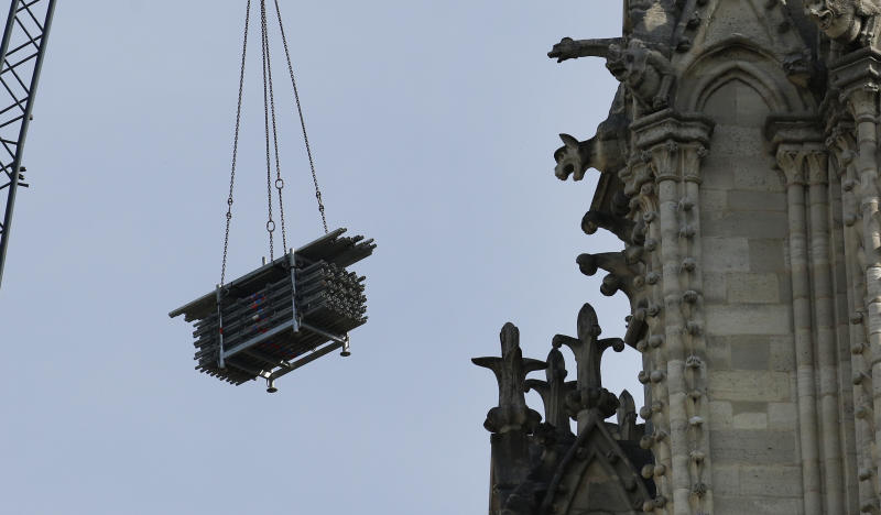 A crane hoists scaffolding past gargoyles outside the Notre Dame Cathedral in Paris, Thursday, April 18, 2019. Nearly $1 billion has already poured in from ordinary worshippers and high-powered magnates around the world to restore Notre Dame Cathedral in Paris after a massive fire. (AP Photo/Christophe Ena)