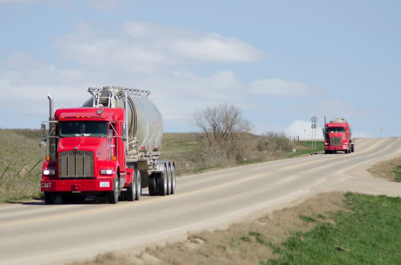 Halliburton oil trucks drive near the company's yard in Williston