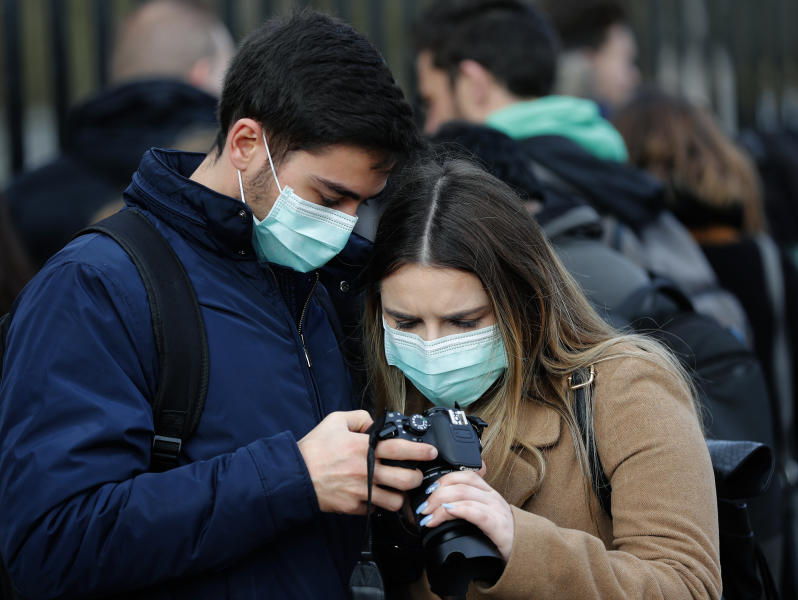 A couple wearing face masks to protect against the Coronavirus outbreak as they look at their photographs after visiting Buckingham Palace in London, Saturday, March 14, 2020. For most people, the new coronavirus causes only mild or moderate symptoms, such as fever and cough. For some, especially older adults and people with existing health problems, it can cause more severe illness, including pneumonia. (AP Photo/Frank Augstein)