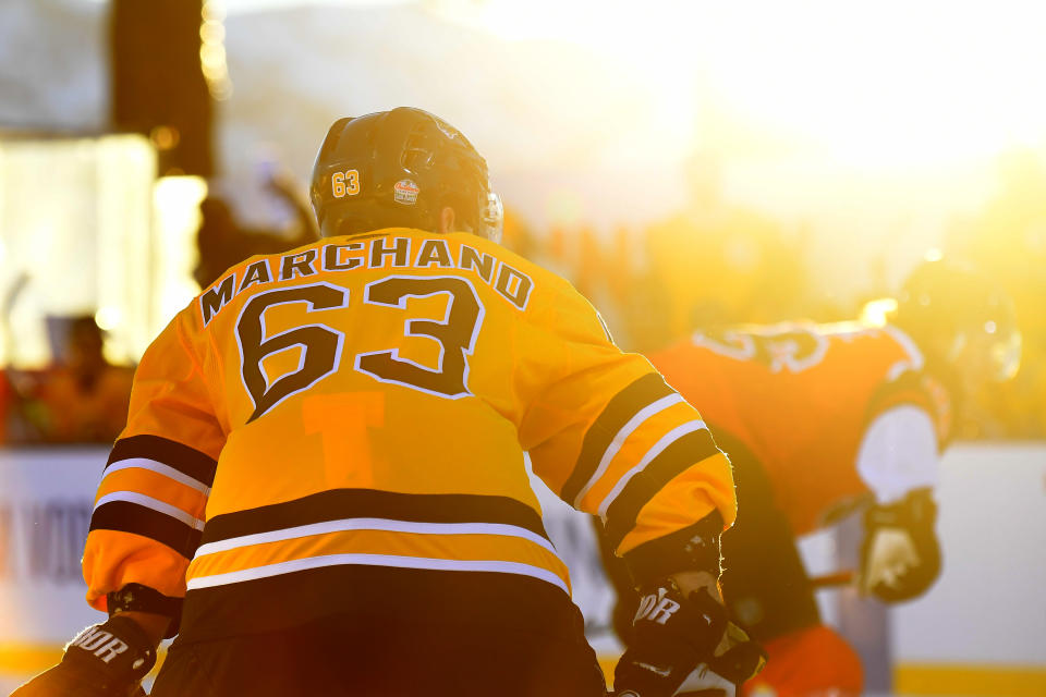 <p>Brad Marchand #63 of the Boston Bruins is seen in the sunset while playing against the Philadelphia Flyers during the first period of the 2021 NHL Outdoors Sunday presented by Honda on the 18th fairway of the Edgewood Tahoe Resort, at the south shore of Lake Tahoe on February 21, 2021 in Stateline, Nevada. (Photo by Brian Babineau/NHLI via Getty Images)</p>