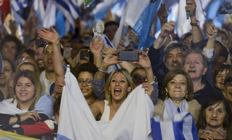 Supporters of opposition presidential candidate Luis Lacalle Pou react at the party's headquarters as they wait for results after a runoff elections in Montevideo, Uruguay, Sunday, Nov. 24, 2019. Uruguayans are choosing between Presidential candidate for the ruling party Broad Front Daniel Martinez and Lacalle. (AP Photo/Santiago Mazzarovich)