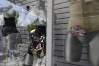 Rocio, 50, who began sex work for the first time last year after losing her $200/month job as a house cleaner due to the coronavirus pandemic, is reflected in the display window of a lingerie shop in central Mexico City, Thursday, March 25, 2021. Unable to find a new job as a cleaner that paid more than half of her previous one, Rocio decided to try sex work; after an initial spike of interest as a new woman on the street, she found herself still earning far less than her previous salary, and struggling to support her family. (AP Photo/Rebecca Blackwell)