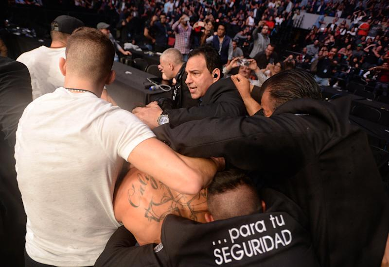 Sep 21, 2019; Mexico City, MEX; Jeremy Stephens (blue gloves) is escorted by security out of the octagon after his fight against Yair Rodriguez (red gloves) ended after being poked in the eye during UFC Fight Night at Mexico City Arena. Mandatory Credit: Orlando Ramirez-USA TODAY Sports