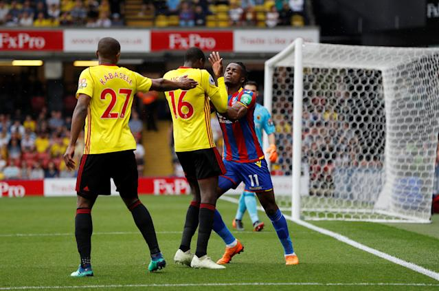 """Soccer Football - Premier League - Watford v Crystal Palace - Vicarage Road, Watford, Britain - April 21, 2018 Crystal Palace's Wilfried Zaha clashes with Watford's Abdoulaye Doucoure REUTERS/Darren Staples EDITORIAL USE ONLY. No use with unauthorized audio, video, data, fixture lists, club/league logos or """"live"""" services. Online in-match use limited to 75 images, no video emulation. No use in betting, games or single club/league/player publications. Please contact your account representative for further details."""