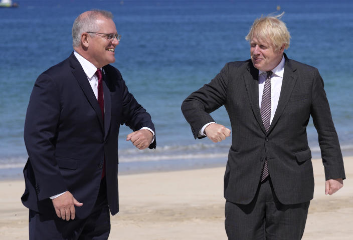 British Prime Minister Boris Johnson, right, greets Australia's Prime Minister Scott Morrison during arrivals for the G7 meeting at the Carbis Bay Hotel in Carbis Bay, St. Ives, Cornwall, England, Saturday, June 12, 2021. Leaders of the G7 gather for a second day of meetings on Saturday, in which they will discuss COVID-19, climate, foreign policy and the economy. (AP Photo/Kirsty Wigglesworth, Pool)