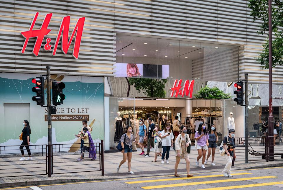 HONG KONG, CHINA - 2021/08/07: Pedestrians cross the street in front of the Swedish multinational clothing design retail company Hennes & Mauritz, H&M, store in Hong Kong. (Photo by Budrul Chukrut/SOPA Images/LightRocket via Getty Images)