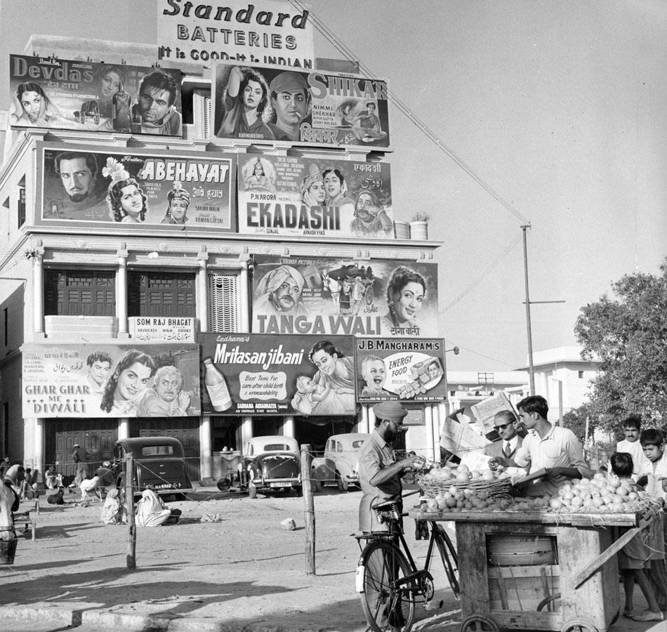 circa 1950:  A man buying fruit from a street stall in front of an advertising hoarding promoting several films in New Delhi, India.  (Photo by Richard Harrington/Three Lions/Getty Images)