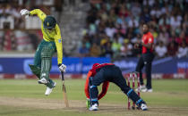 South Africa's batsman Dwaine Pretorius, left, jumps as he avoids a run out from England's Jos Buttler during the 2nd T20 cricket match between South Africa and England at Kingsmead stadium in Durban, South Africa, Friday, Feb. 14, 2020. (AP Photo/Themba Hadebe)