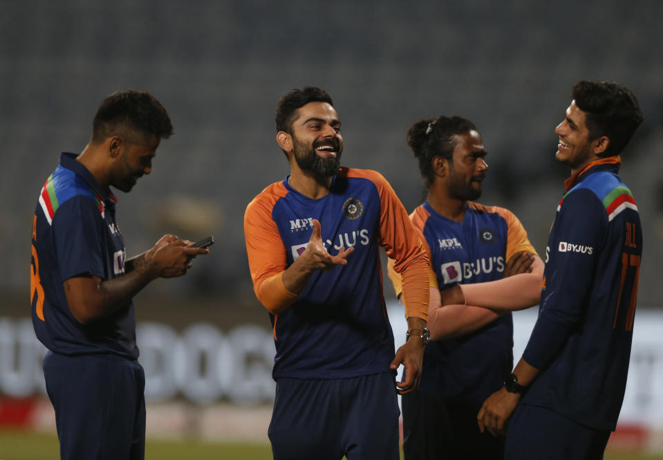 India's captain Virat Kohli, second left, shares a light moment with teammates after their win in the third One Day International cricket match between India and England at Maharashtra Cricket Association Stadium in Pune, India, Sunday, March 28, 2021. (AP Photo/Rafiq Maqbool)