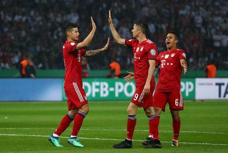 Soccer Football - DFB Cup Final - Bayern Munich vs Eintracht Frankfurt - Olympiastadion, Berlin, Germany - May 19, 2018 Bayern Munich's Robert Lewandowski celebrates scoring their first goal with James Rodriguez and Thiago Alcantara REUTERS/Michael Dalder DFB RULES PROHIBIT USE IN MMS SERVICES VIA HANDHELD DEVICES UNTIL TWO HOURS AFTER A MATCH AND ANY USAGE ON INTERNET OR ONLINE MEDIA SIMULATING VIDEO FOOTAGE DURING THE MATCH.