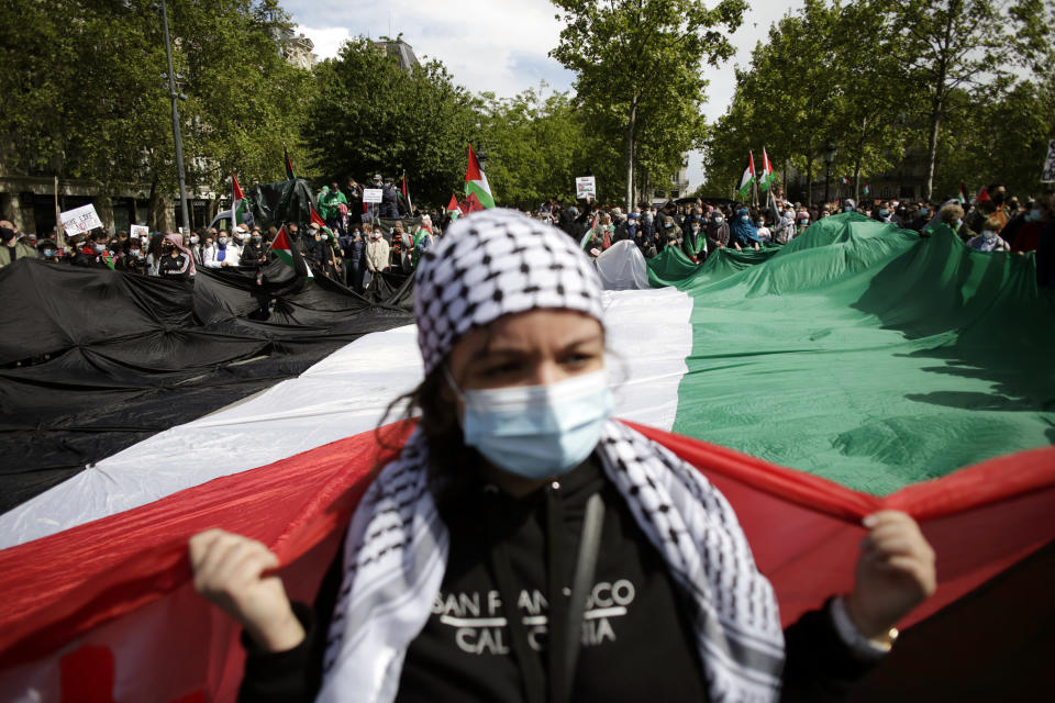Protesters hold a giant Palestinian flag in Paris, Saturday, May 22, 2021, as they take part in a rally supporting Palestinians. Egyptian mediators held talks Saturday to firm up an Israel-Hamas cease-fire as Palestinians in the Hamas-ruled Gaza Strip began to assess the damage from 11 days of intense Israeli bombardment.Supporters of the Palestinians. (AP Photo/Thibault Camus)