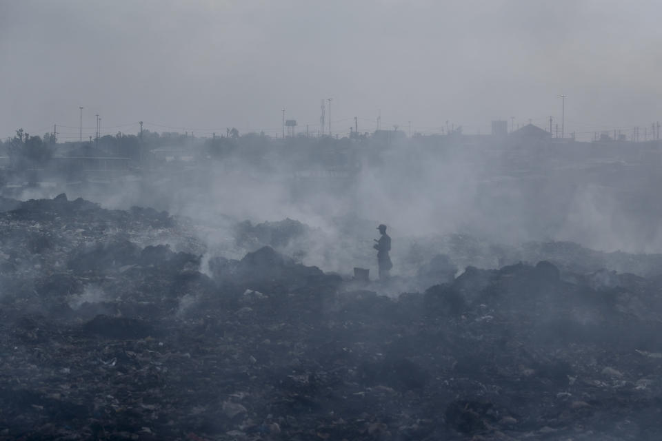 """A man who scavenges recyclable materials for a living walks across a mountain of garage amidst smoke from burning trash at Dandora, the largest garbage dump in the capital Nairobi, Kenya Tuesday, Sept. 7, 2021. Tuesday marks the second """"International Day of Clean Air for blue skies"""" aimed at rallying countries to recognize and combat the environmental risks to human health posed by air pollution, according to the United Nations. (AP Photo/Brian Inganga)"""