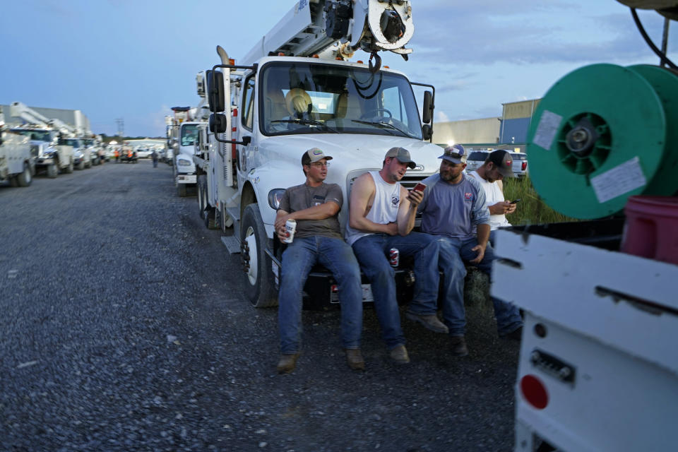 Workers from Southwest Arkansas Electric, of Texarkana, Ark., relax on their truck after a day's work, inside a tent city for electrical workers in Amelia, La., Thursday, Sept. 16, 2021. In the wake of hurricanes, one of the most common and comforting sites is the thousands of electric workers who flow into a battered region when the winds die down to restore power and a sense of normalcy. (AP Photo/Gerald Herbert)