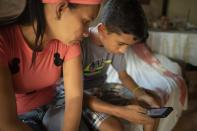 Samuel Andres Mendoza checks his Twitter account, where he sells his drawings, with his mother Magdalena Rodriguez at their home in Barquisimeto, Venezuela, Tuesday, March 2, 2021. Rodriguez finds it difficult to afford the relatively expensive high-protein foods that doctors say her teen needs to deal with a form of malnutrition. (AP Photo/Ariana Cubillos)