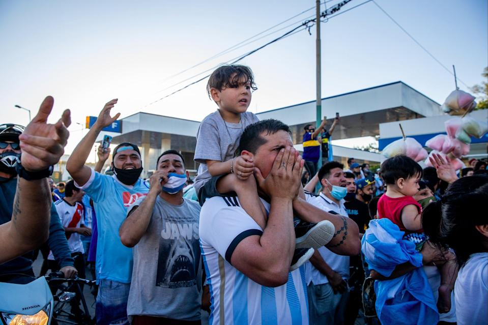 Fans cheer and shout to pay tribute during the burial ceremony of Argentine football legend Diego Maradona (Getty Images)