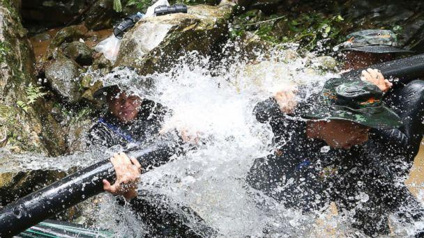 PHOTO: Thai soldiers try to connect water pipes that will help bypass water from entering a cave where 12 boys and their soccer coach have been trapped since June 23, in Mae Sai, Chiang Rai province, in northern Thailand, July 7, 2018. (Sakchai Lalit/AP)