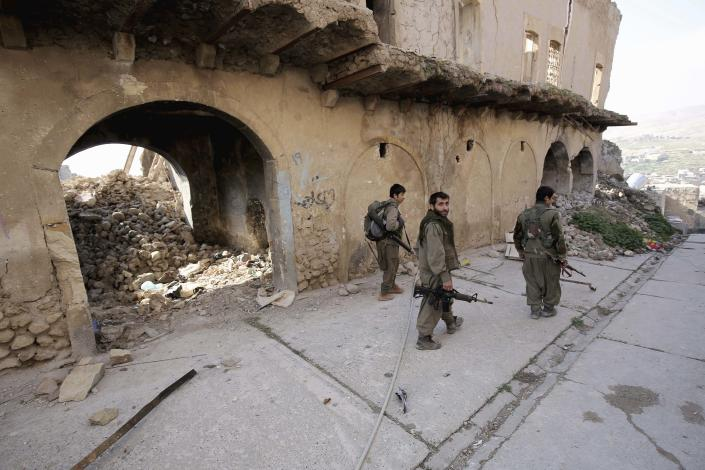 FILE - In this Thursday, Jan. 29, 2015 file photo, fighters of the Turkey-based Kurdish Workers' Party (PKK) walk in the damaged streets of Sinjar, Iraq. Turkey said Wednesday, June 17, 2020, it has airlifted troops for a cross-border ground operation against Kurdish militants in northern Iraq. Turkey regularly carries out air and ground attacks against the outlawed Kurdistan Workers Party, or PKK, which maintains bases in northern Iraq. Wednesday's was the first known airborne land offensive.(AP Photo/Bram Janssen, File)