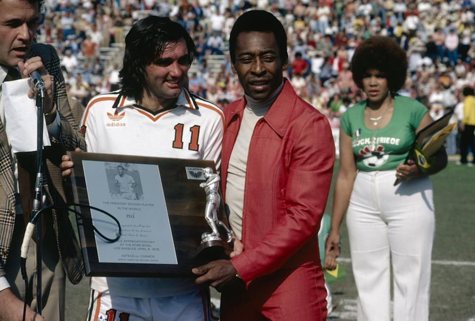 George Best presents Pele with a plaque commemorating the Brazilian as the best soccer player in the world during Pele Appreciation Day at Rose Bowl stadium in Pasedena, California, 9th April 1978. A friendly match was played between the Aztecs and Cosmos to mark the occasion. (Photo by Getty Images)