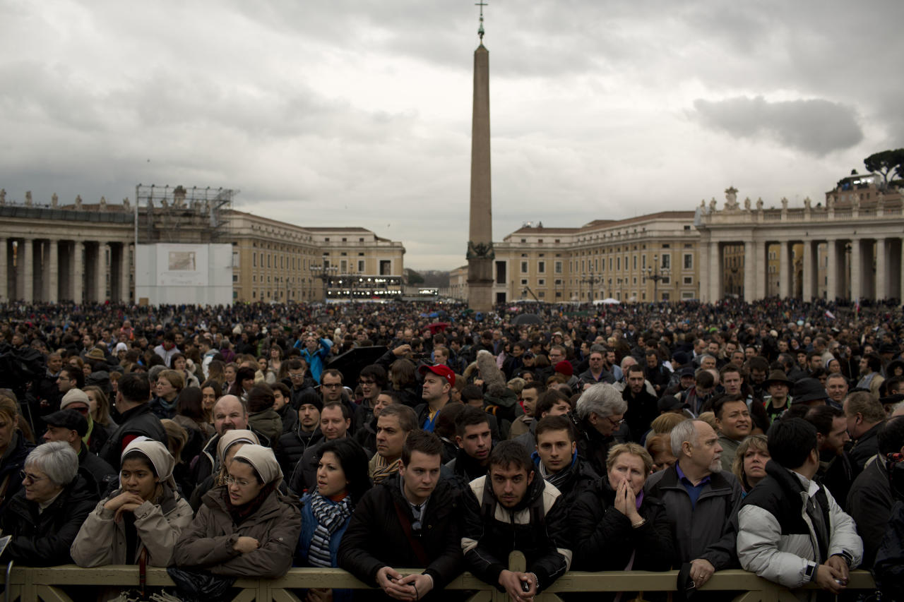 Visitors wait for the chimney smoke in St. Peter's Square during the second day of the conclave to elect a new pope, at the Vatican, Wednesday, March 13, 2013. Black smoke again billowed from the chimney of the Sistine Chapel on Wednesday, meaning that Catholic cardinals hadn't elected a pope on their second or third rounds of balloting. (AP Photo/Oded Balilty)