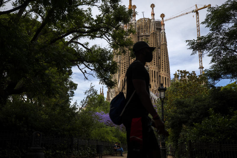 In this Sunday, May 31, 2020 photo, local visitors walk in a park next to the Antoni Gaudí's La Sagrada Familia Basilica in Barcelona. Tourism is a pillar of Spain's economy. Eighty million annual visitors generate 12% of Spain's GDP and help employ 2.6 million people. (AP Photo/Emilio Morenatti)
