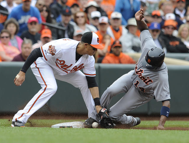 Baltimore Orioles third baseman Manny Machado, left, is unable to hold onto the ball as Detroit Tigers' Austin Jackson steals third in the fourth inning of a baseball game Wednesday, May 14, 2014, in Baltimore. (AP Photo/Gail Burton)