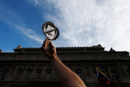 A man carries a sign depicting Venezuelan President Nicolas Maduro, during a demonstration support of Venezuela's opposition leader Juan Guaido, on the Vatican Square in Buenos Aires, Argentina January 23, 2019. REUTERS /Martin Acosta/Files