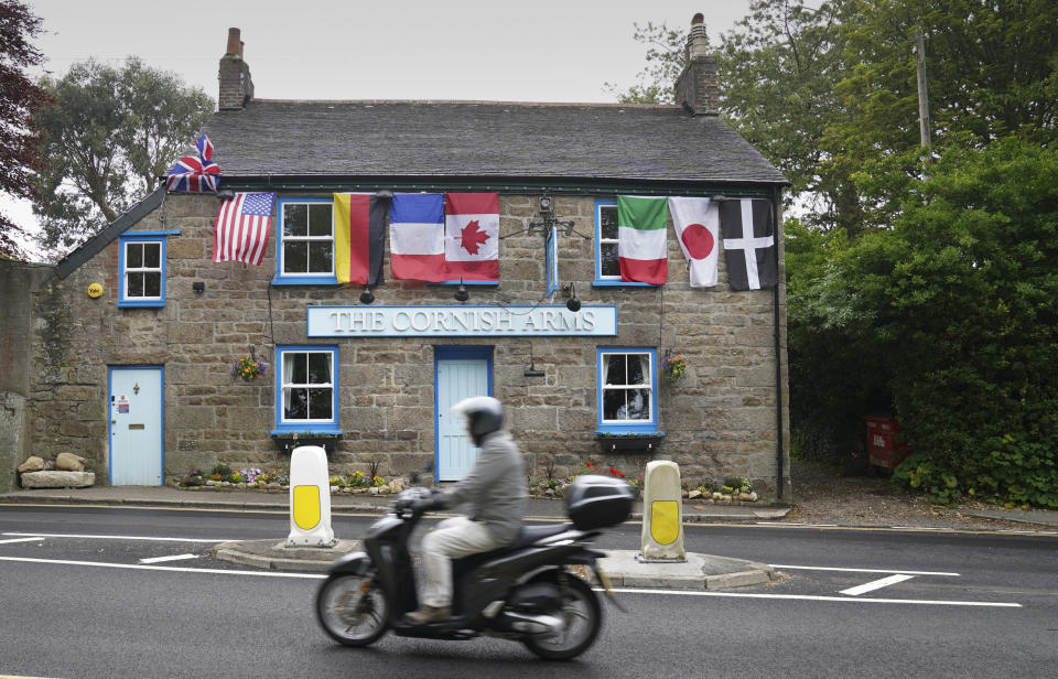 FILE - In this Wednesday, June 9, 2021 file photo, a man rides a motorbike past a pub with flags of the G7 nations and the flag of Cornwall in St. Ives, Cornwall, England. Towering steel fences and masses of police have transformed the Cornish seaside as leaders of the Group of Seven wealthy democracies descent for a summit near St. Ives in Cornwall, a popular holiday destination. A huge frigate dominates the coastline, armed soldiers guard the main sites and some 5,000 extra police officers have been deployed to the area. (AP Photo/Jon Super, File)